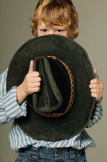 Young boy hiding part of face with large cowboy hat : Stock Photo