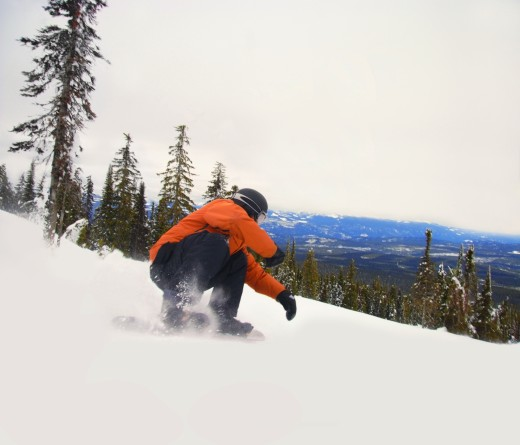 Snowboarder crouching down low as he descends snow hill : Stock Photo