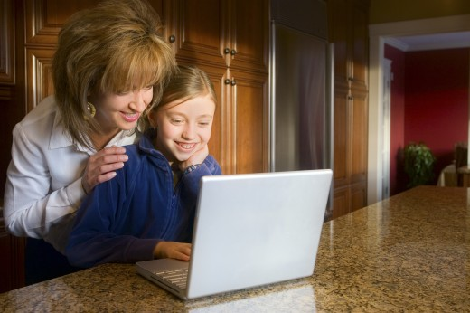 Mother and daughter using computer : Stock Photo