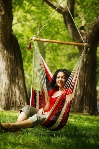 Young adult female sitting on hammock : Stock Photo