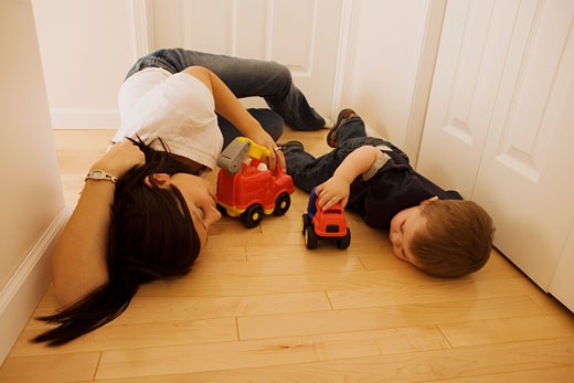 Mother and son laying on the floor playing with toys : Stock Photo