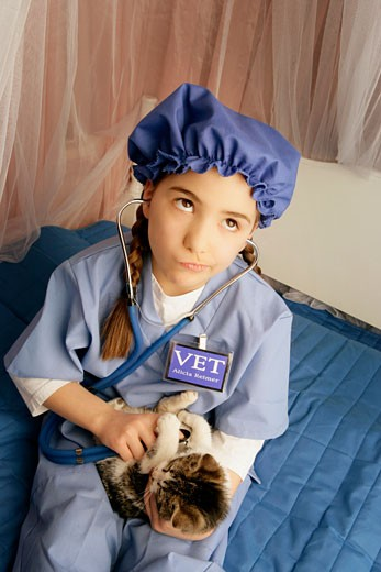 Stock Photo: 1889R-31627 Front view of girl examining cat