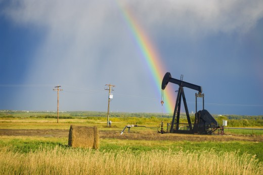 Storm clouds and rainbow over prairie oil pump   : Stock Photo