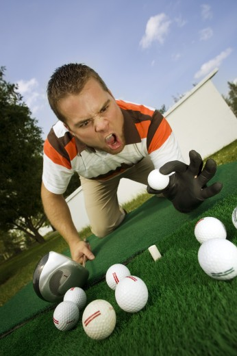 Stock Photo: 1889R-31956 Frustrated golfer yelling at golf balls