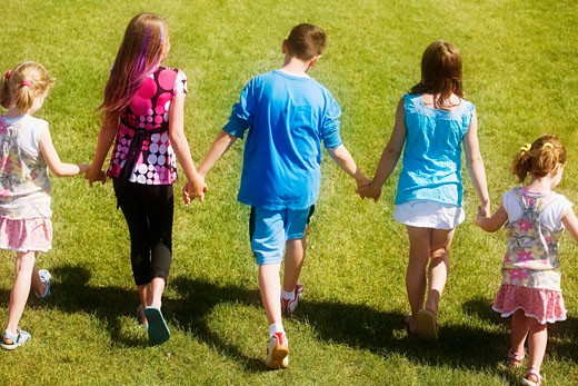 Rear view of a kids walking and holding hands : Stock Photo