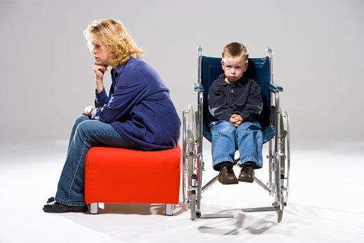 Child in wheelchair with mother sitting beside him : Stock Photo