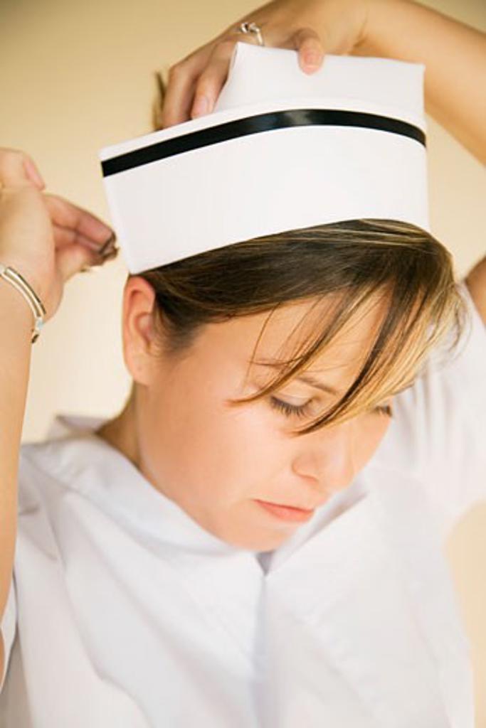 Stock Photo: 1889R-33653 Nurse pinning on cap