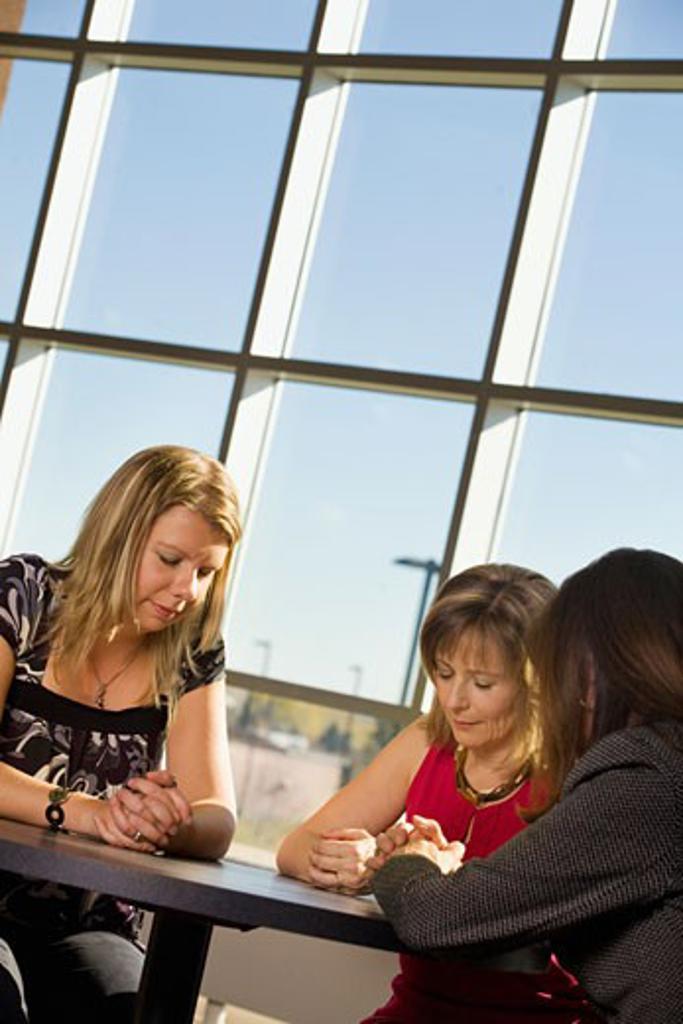 Three women praying : Stock Photo