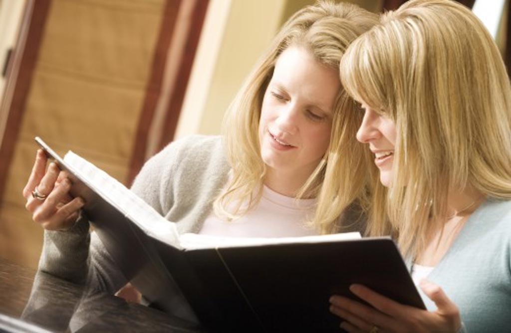 Women looking at photo album : Stock Photo