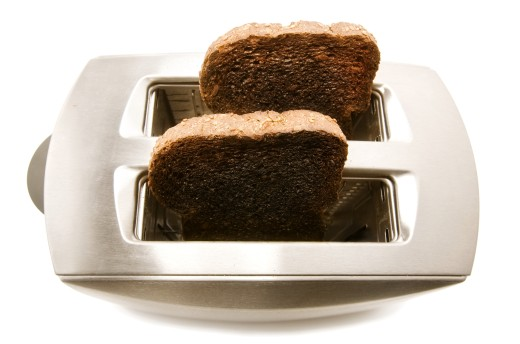 Stock Photo: 1889R-35460 Burnt toast popping out of a toaster