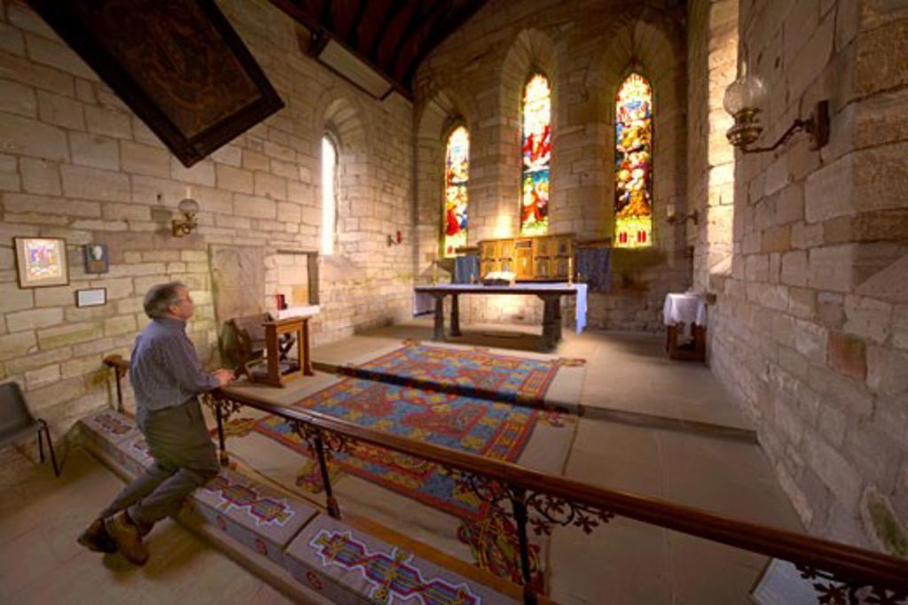 Man praying in chapel, Holy Island, Bewick, England : Stock Photo