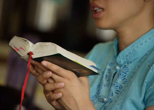 Woman reading from the Bible : Stock Photo