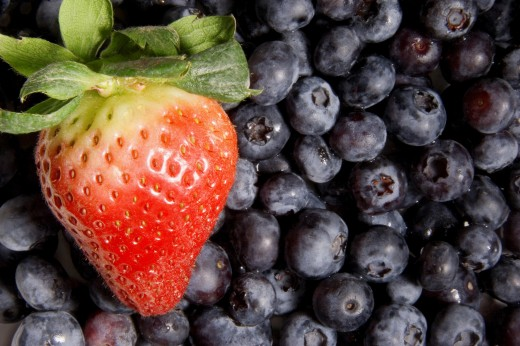 One strawberry on blueberries : Stock Photo