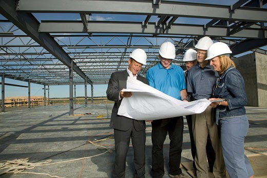 Group of people looking at archtectural drawings : Stock Photo