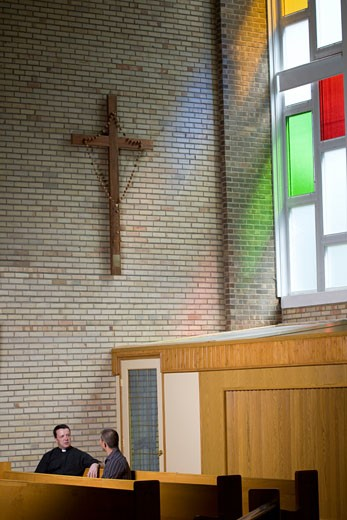 Catholic Priest and a man talking in a church : Stock Photo