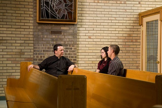 Catholic Priest talking with a young couple : Stock Photo