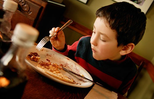 Boy eating breakfast : Stock Photo