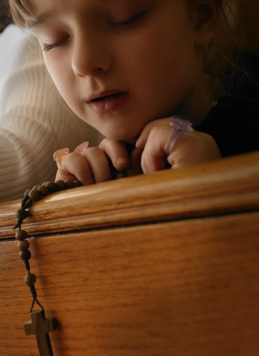 Young girl holding rosary beads while praying with eyes closed : Stock Photo