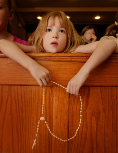 Young girl holding rosary beads over pew : Stock Photo