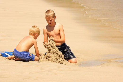 Stock Photo: 1889R-4112 Brothers building sandcastle on beach