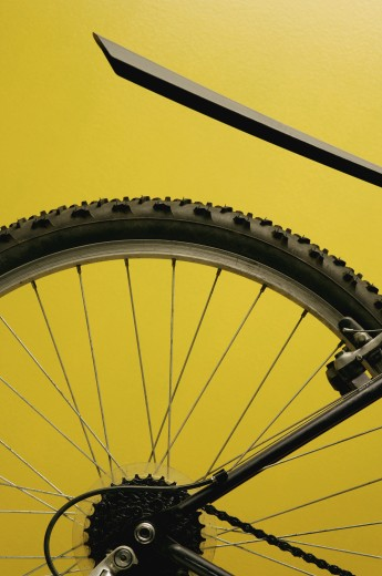 Stock Photo: 1889R-4183 Rear bicycle wheel against yellow background