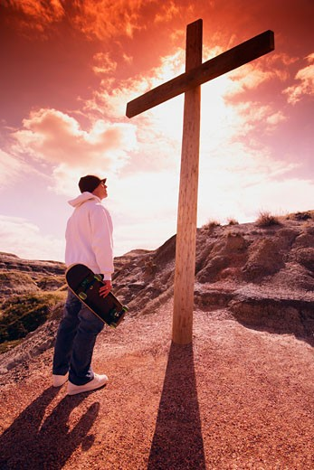 Skateboarder standing before a cross : Stock Photo