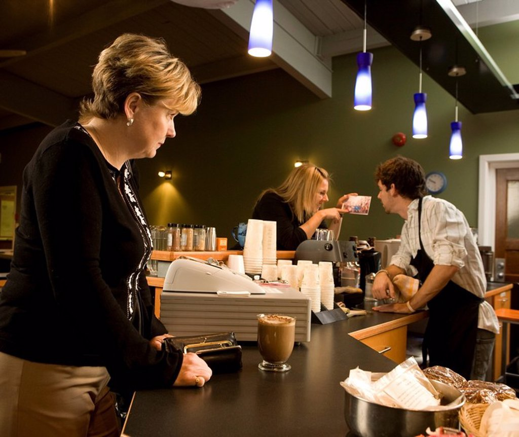 Woman waiting at counter while barista talks : Stock Photo