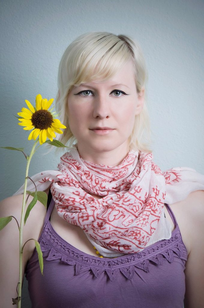 Stock Photo: 1889R-46991 Woman holding a daisy with missing petals