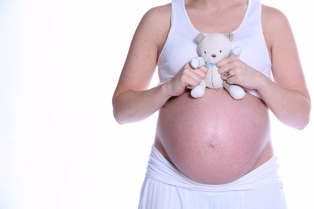Pregnant woman holding teddy bear over bare belly : Stock Photo