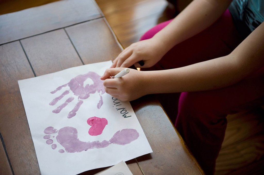 Girl making hand and footprints on paper : Stock Photo