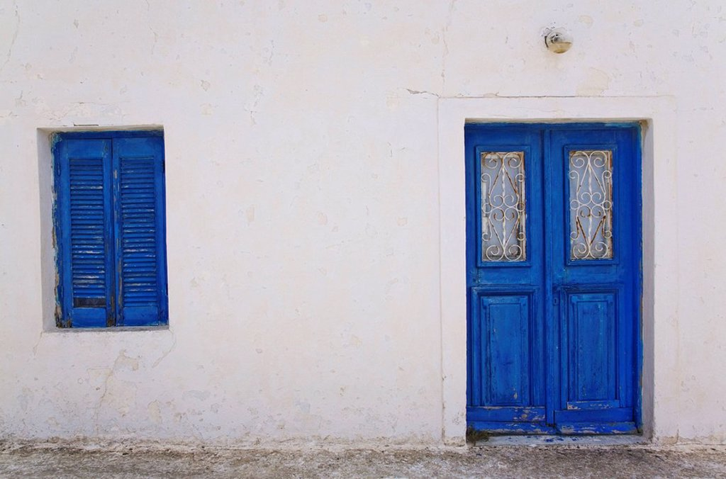 Traditional Greek architectural style building facade with blue painted doors and window shutters in Pyrgos village, Santorini, Greece : Stock Photo