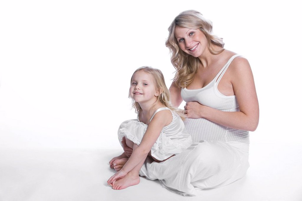 Pregnant woman sitting with her daughter : Stock Photo