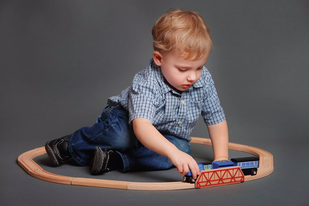 Boy playing with toy train : Stock Photo