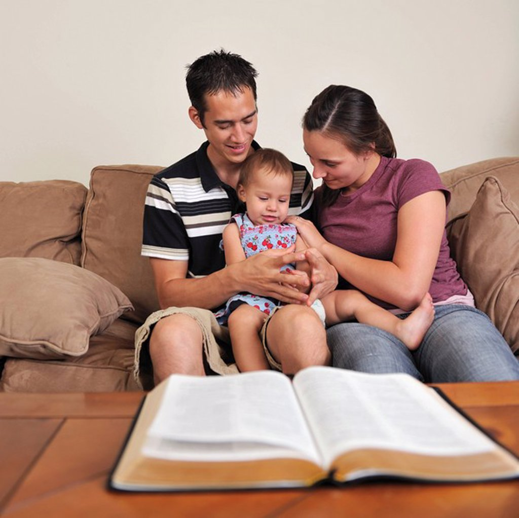 A young Christian family praying together : Stock Photo