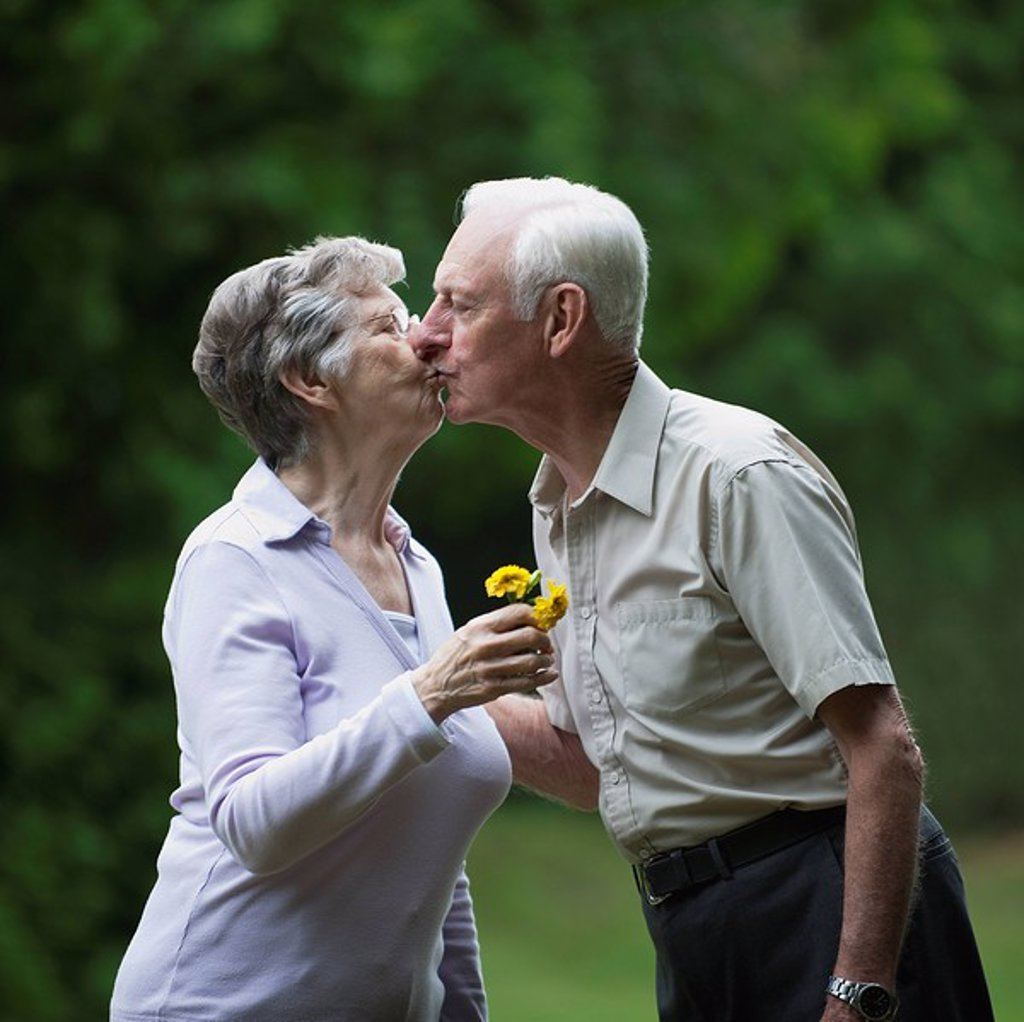 An elderly couple kissing : Stock Photo