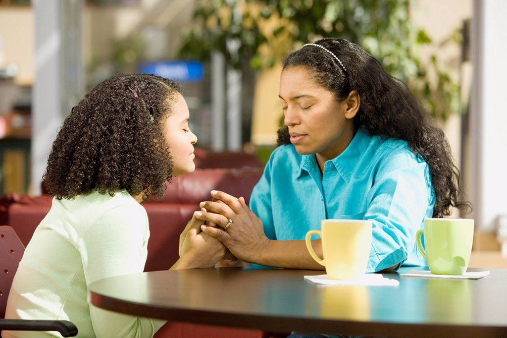 Hispanic mother and daughter praying in coffee shop : Stock Photo
