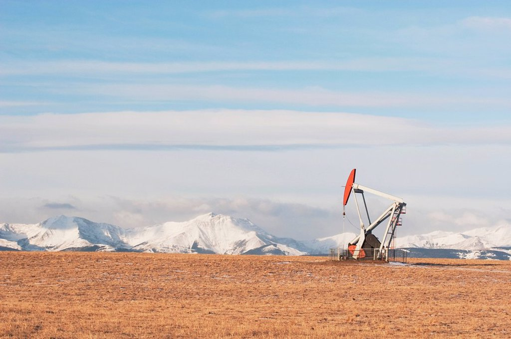 Stock Photo: 1889R-49411 alberta, canada, pump jack in a brown field with snow covered mountains in the background