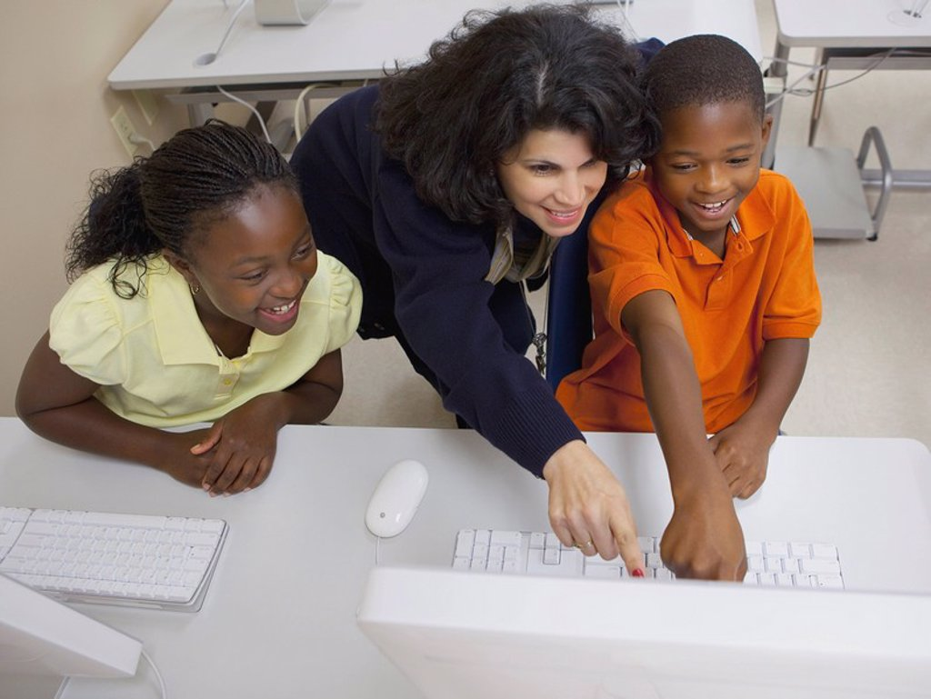 teacher working with students in computer class : Stock Photo
