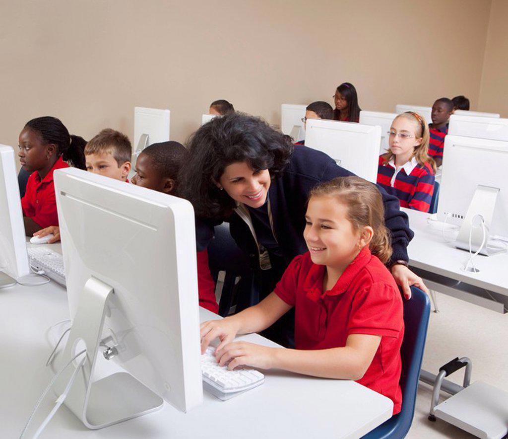 teacher helping student in computer class : Stock Photo