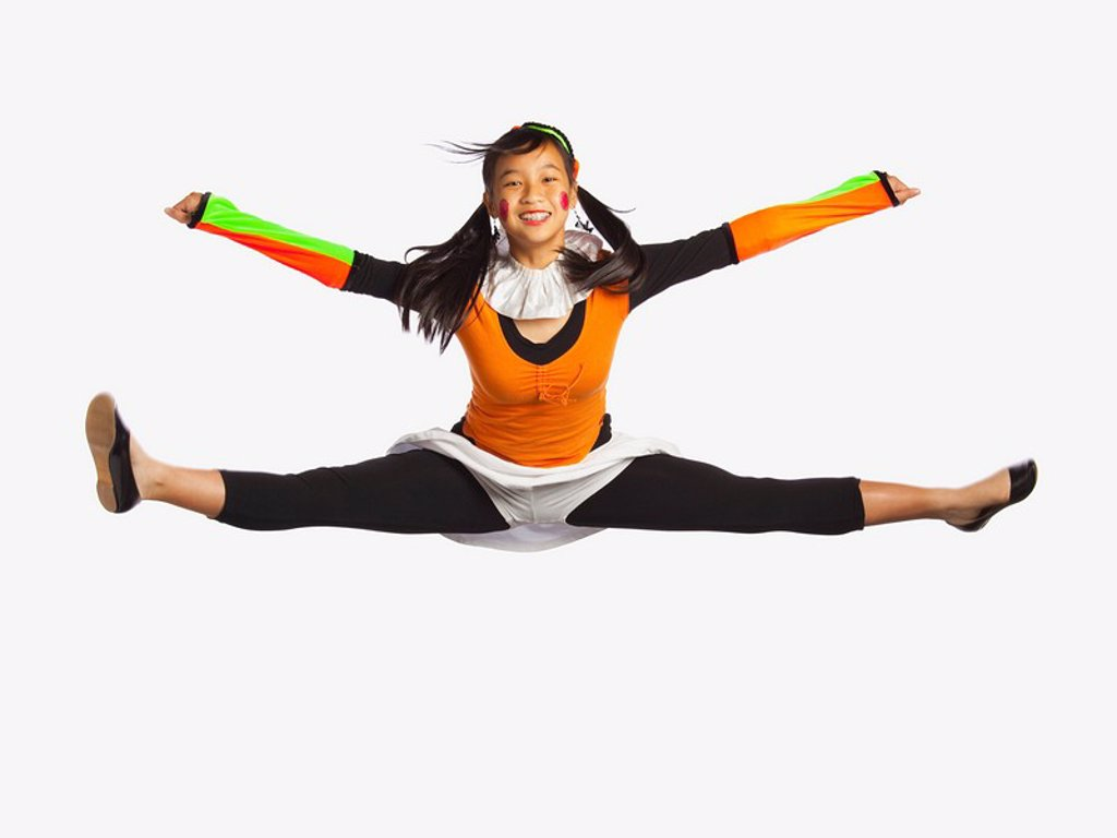 Stock Photo: 1889R-50624 girl jumping with legs and arms outstretched