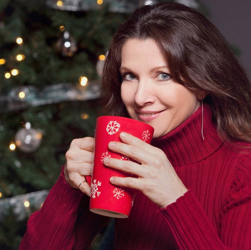 woman sipping a hot beverage by the christmas tree : Stock Photo