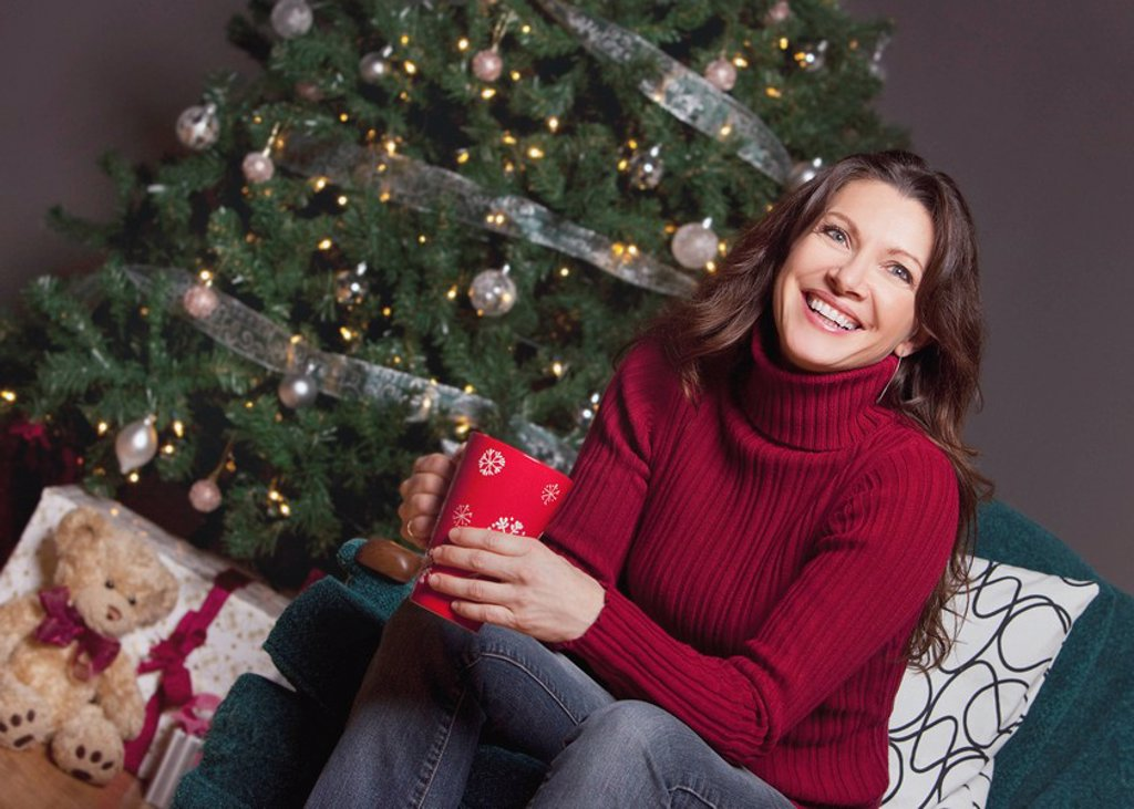woman sitting by the christmas tree : Stock Photo