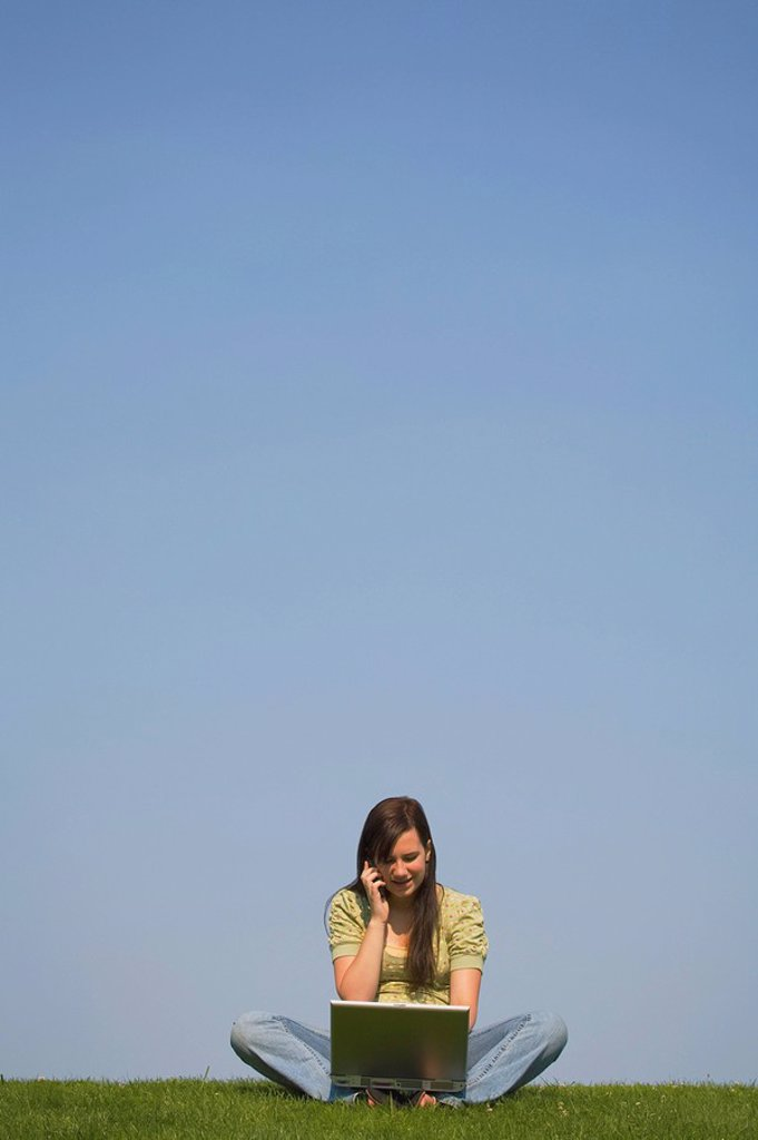 Stock Photo: 1889R-51456 a girl working on a laptop and talking on a cellphone while sitting on the grass