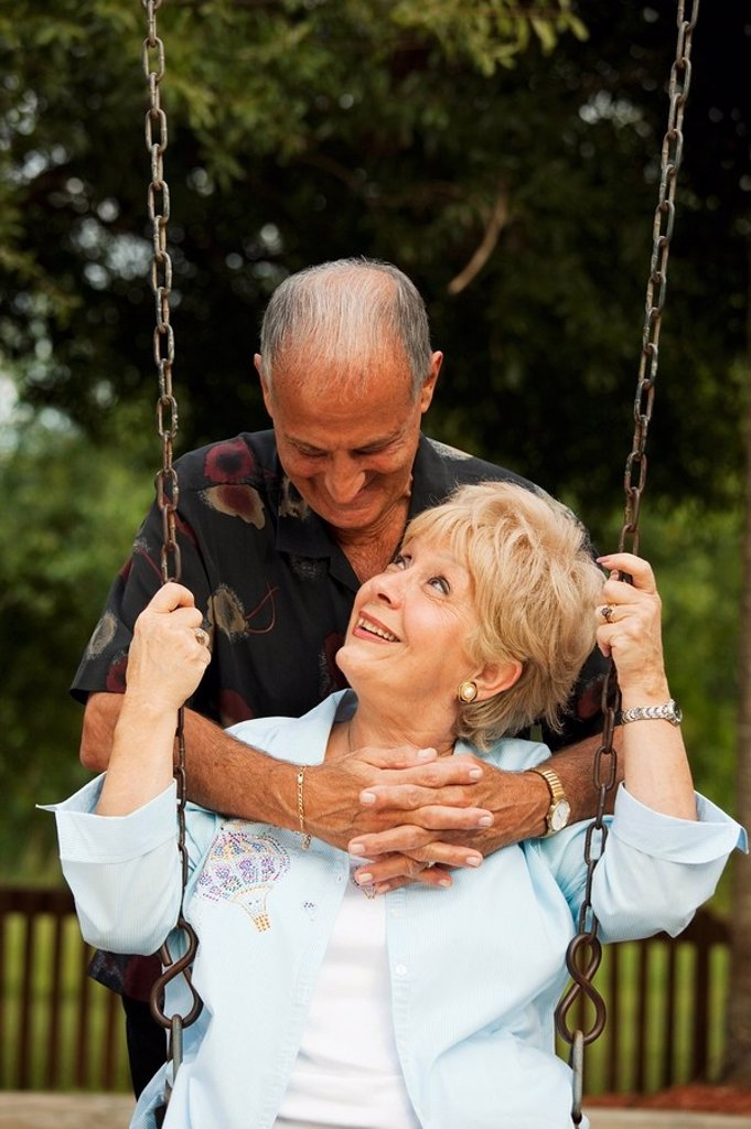 Stock Photo: 1889R-51498 fort lauderdale, florida, united states of america, a couple with the woman sitting on a swing