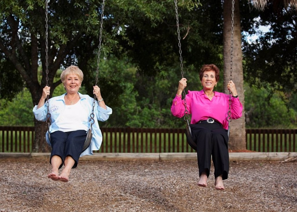 Stock Photo: 1889R-51506 fort lauderdale, florida, united states of america, two women on the swings