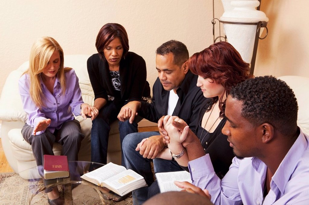 Stock Photo: 1889R-51551 a group of adults praying together with their bibles open