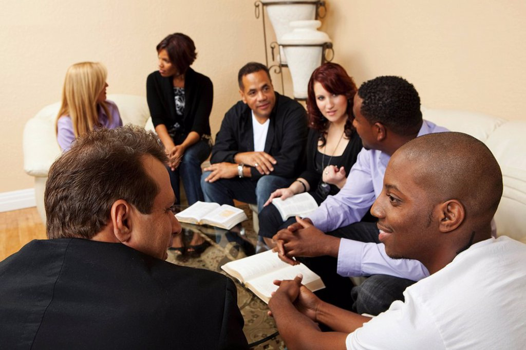 a group of adults in a home bible study : Stock Photo