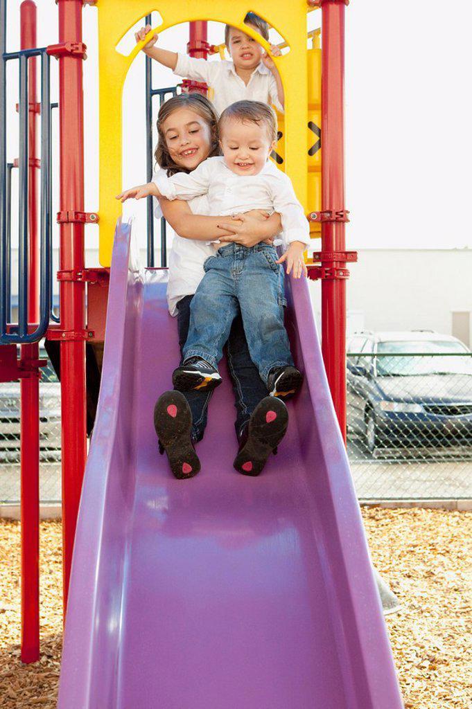 three children playing at the playground : Stock Photo