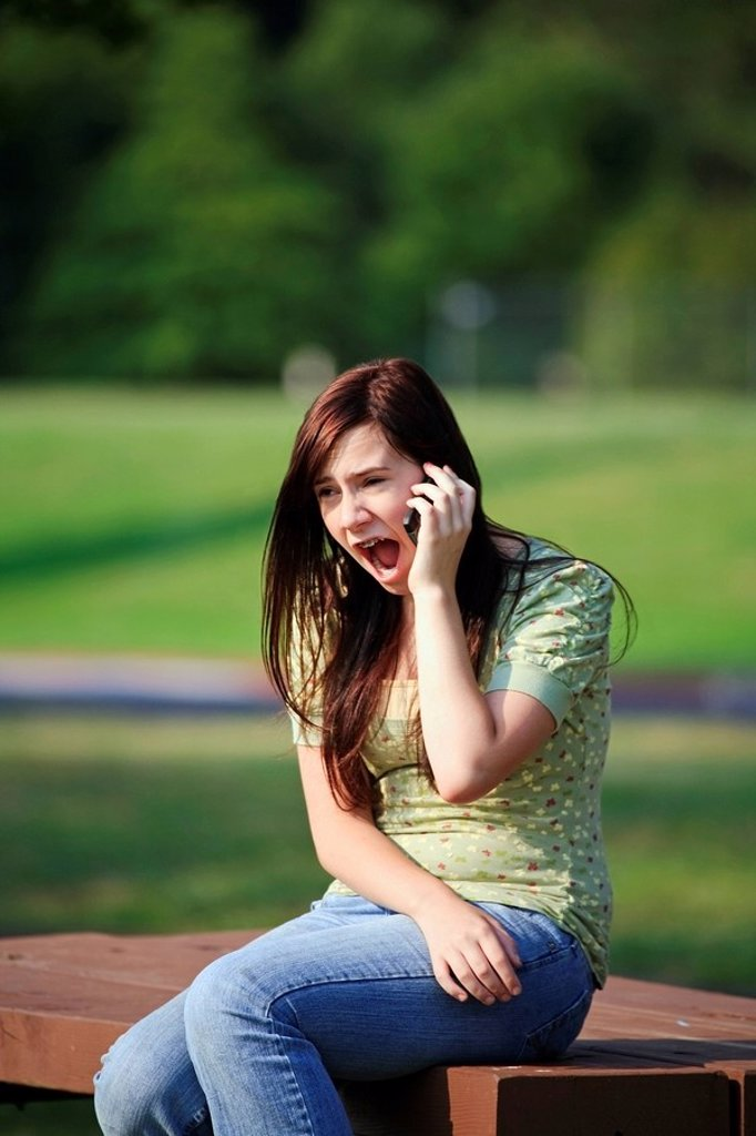 a girl talking on her cell phone with a surprised look : Stock Photo