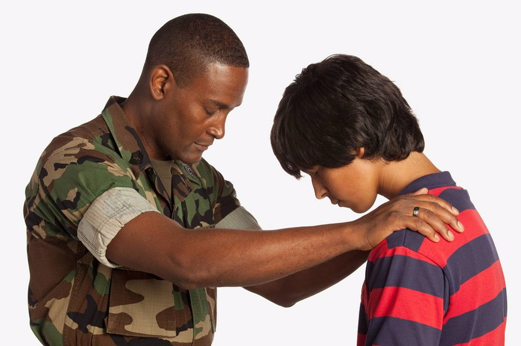 a military man praying for a teenage boy : Stock Photo